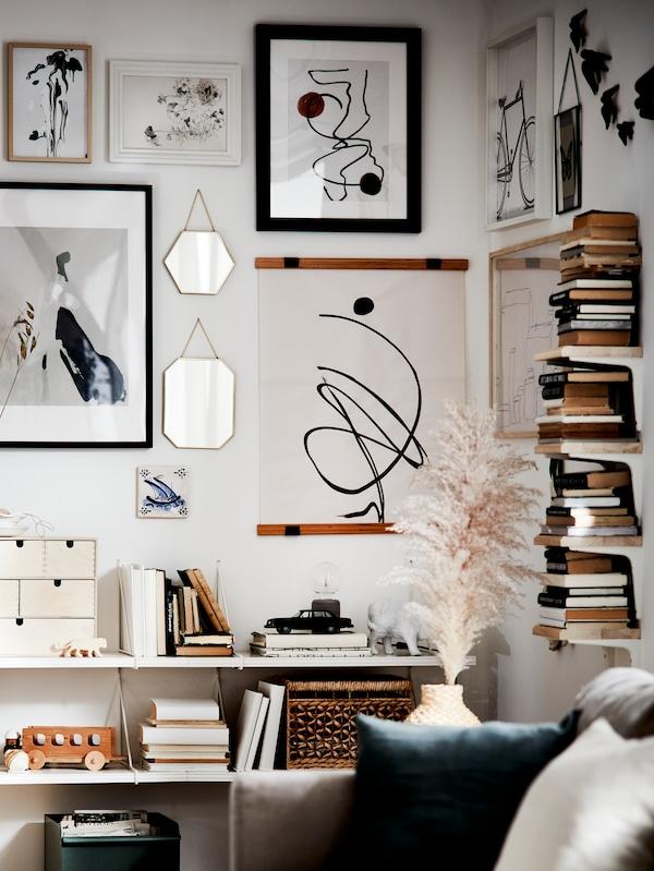 Pareti con specchi dorati, poster incorniciati di diversi colori e misure e mensole bianche.