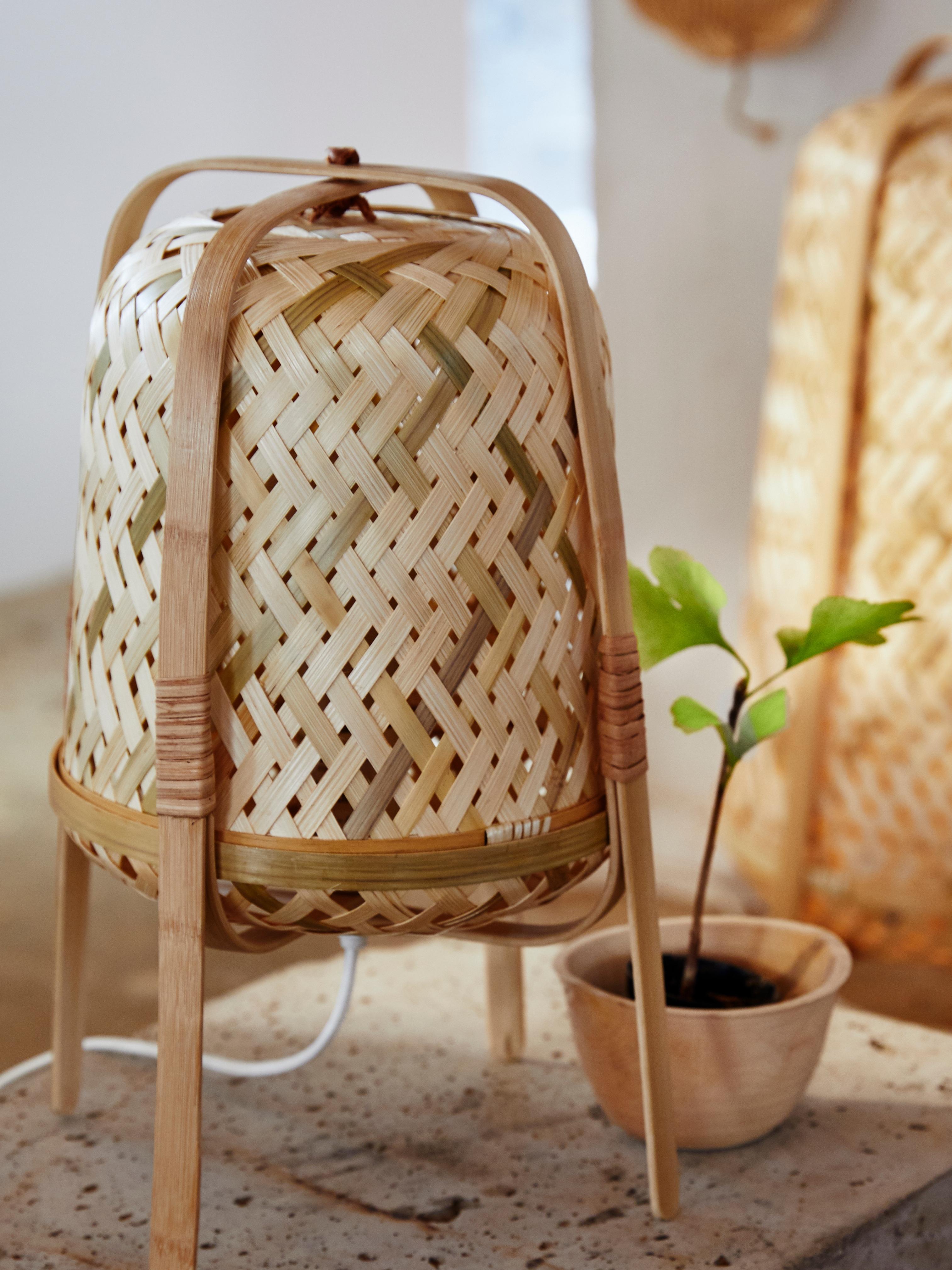 KNIXHULT stolna lampa od bambusa, koju su ručno istkali vješti majstori, pored tegle sa zelenom biljkom na stolu.