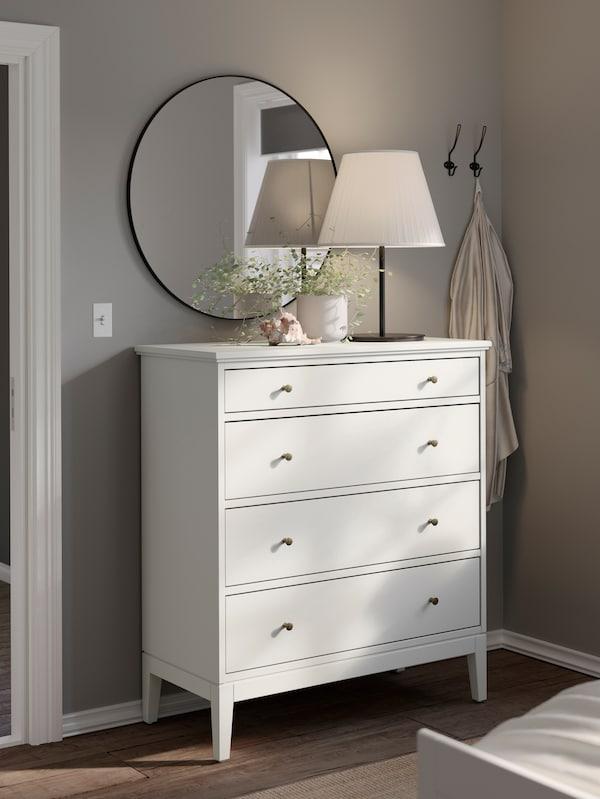 Rincón de un dormitorio con una cómoda IDANÄS blanca, una lámpara y una planta sobre la cómoda, y un espejo redondo encima, en la pared.