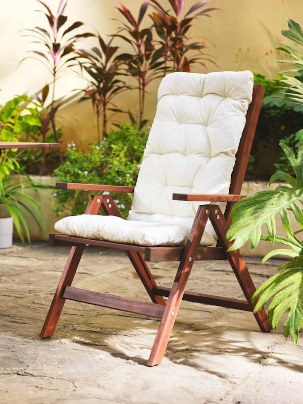En hvilestol af træ, der står udenfor og har en beige hynde på.