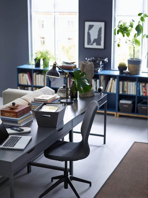 A warm home office with a natural wood desk and a pink char pulled up to it.