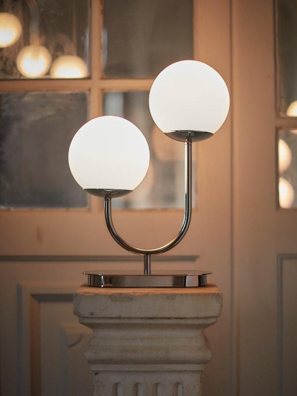 Lampa s dvomi okrúhlymi sklenenými tienidlami na kovovom ráme postavená na bielom stĺpe s oknom v pozadí.