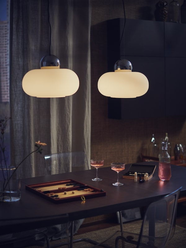 A smoked glass/white TONVIS table lamp stands on a white surface against a wall covered with light brown wallpaper.