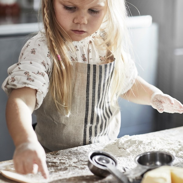 Dlouhovlasé děvče vbéžové zástěře série MARIATHERES si hraje smoukou na pracovním stole.