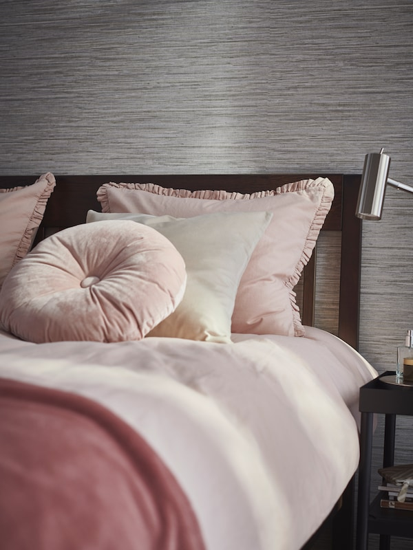 In a bedroom, a KRANSBORRE cushion, SANELA cushion cover, and pink KRANSKRAGE duvet cover set are on a tidy bed.