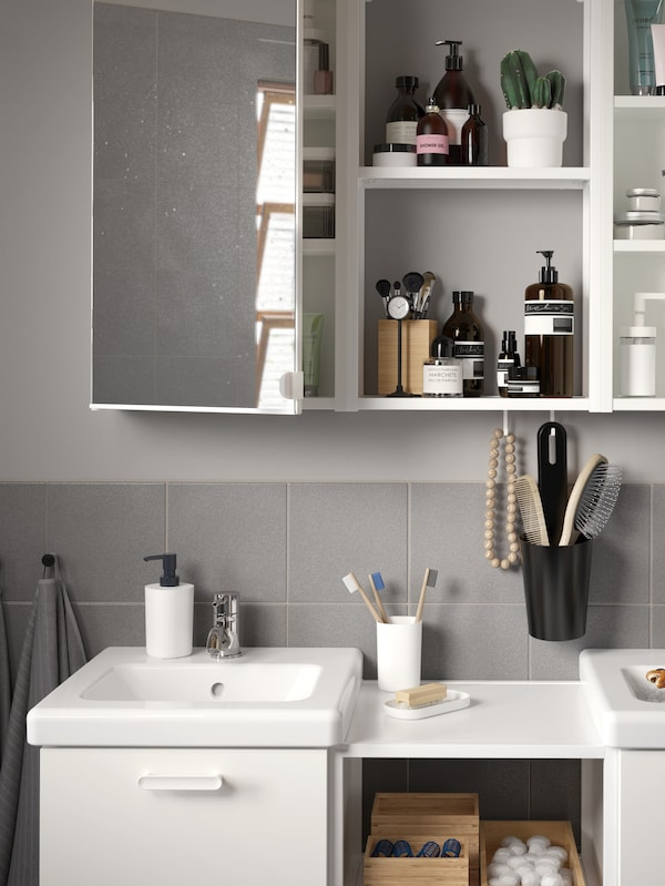 Un baño gris que ten 2 mobles de lavabo brancos con caixóns e un armario cunha porta con espello aberta e estantes abertos a carón del.