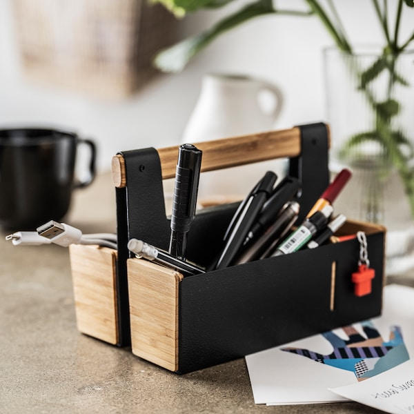 A portable desk organizer in bamboo/black filled with pens stands on a stone-effect surface.