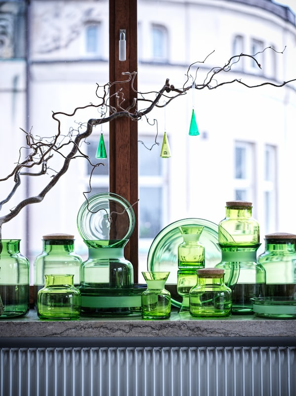 Three VINTER 2021 hanging decorations hang from a branch in a window above VINTER 2021 glass vases and jars.
