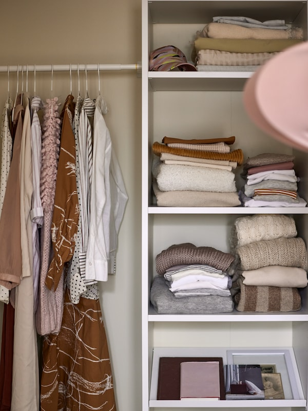 A white AURDAL shelving unit with folded clothes inside, with a clothes rack on the side with clothes on hangers.