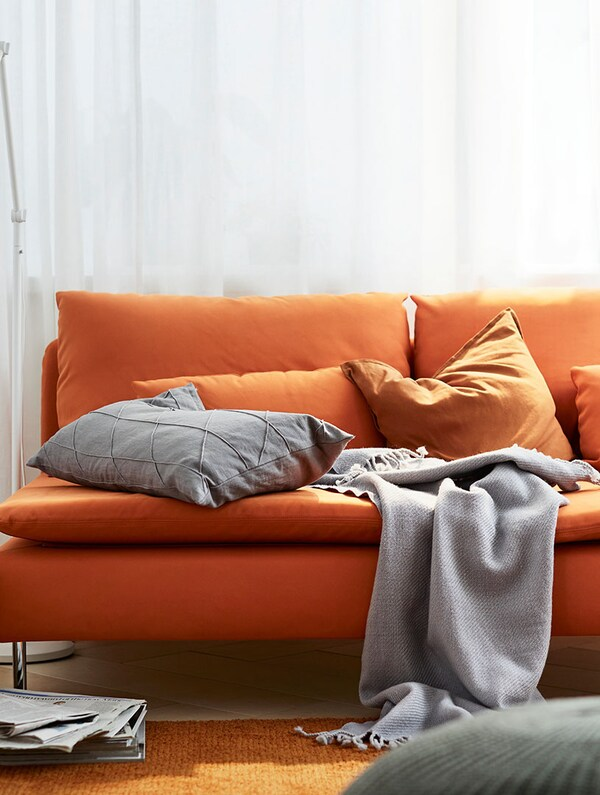 An orange 3-seat sofa with grey and orange cushions and a grey throw on top stands in front of closed white curtains.