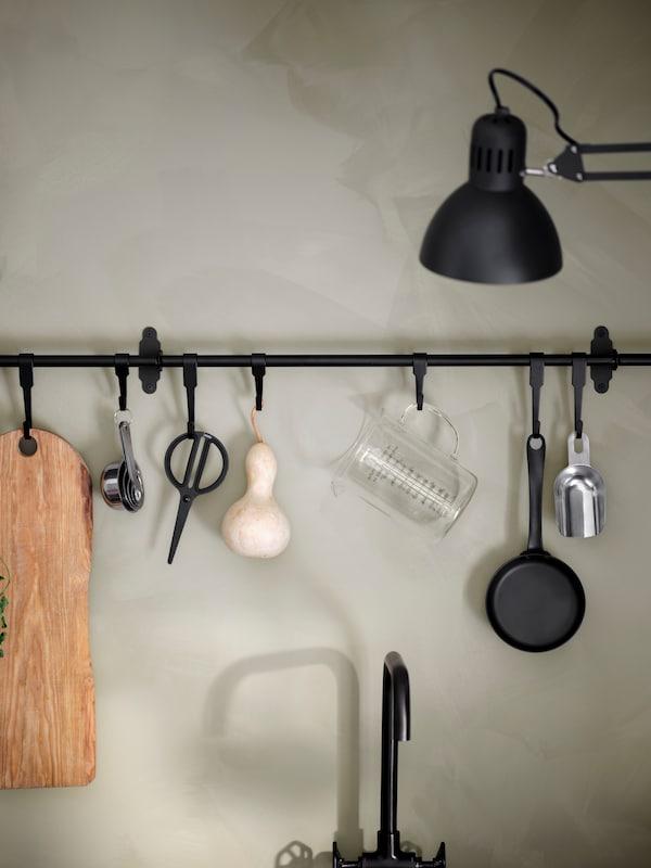 Een zwarte HULTARP rail tegen een grijze keukenmuur. Aan de HULTARP haken hangt een braadpan en keukengerei.