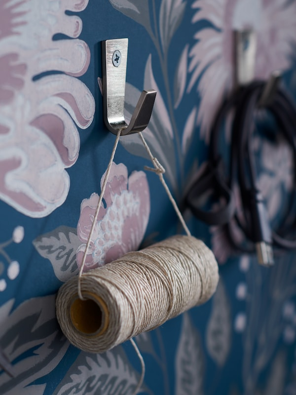 A roll of twine hanging on a hook in front of a dark blue wallpaper with pink flowers.