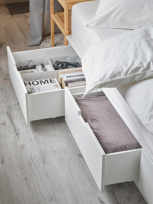 هيكل سرير NORDLI أبيض مع تخزين من أسفل. اثنان من الأدراج مفتوحة وتحتوي على كتب وغطاء سرير وأغراض متعددة.