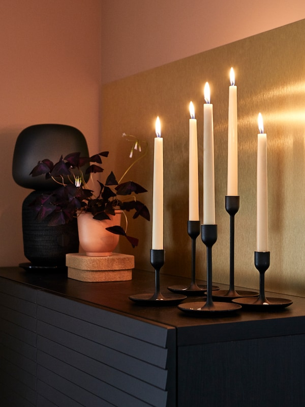 Lit candles in black candle holders, a potted plant and a speaker lamp, with a LYSEKIL brass-coloured wall panel behind.