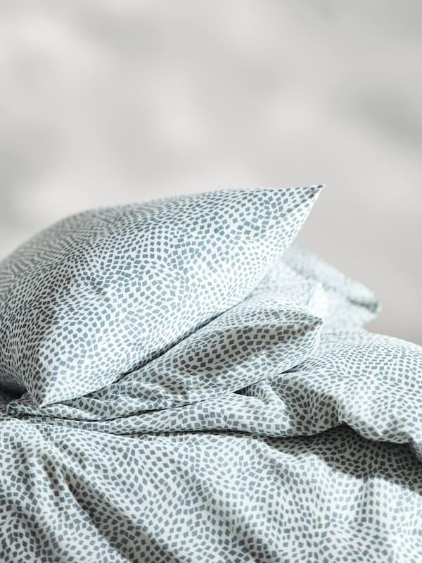 Une couette et des oreillers recouverts du linge de lit bleu et blanc TRÄDKRASSULA, empilés, avec les oreillers sur le dessus