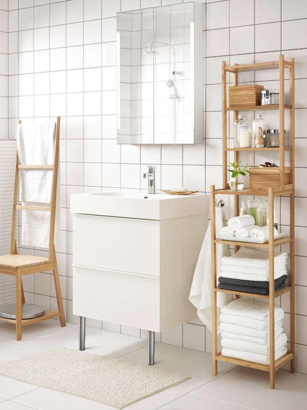 A bright and white-tiled bathroom with a RÅGRUND shelf unit in bamboo stocked with towels, beauty products and boxes.