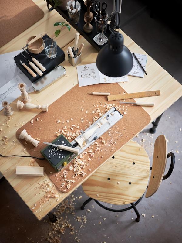 مكتبانخشب صنوبرولبادتين لسطح المكتب مصنوعتان من الفلينومصباح عمل رمادي داكنوأدوات نحت خشبوأغراض خشبية.
