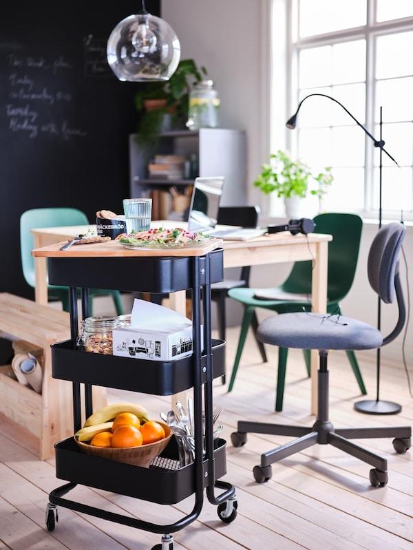 Černý vozík RÅSKOG s jídlem a jídelními doplňky stojí u borovicového stolu INGO. Nad stolem visí lampa JAKOBSBYN.
