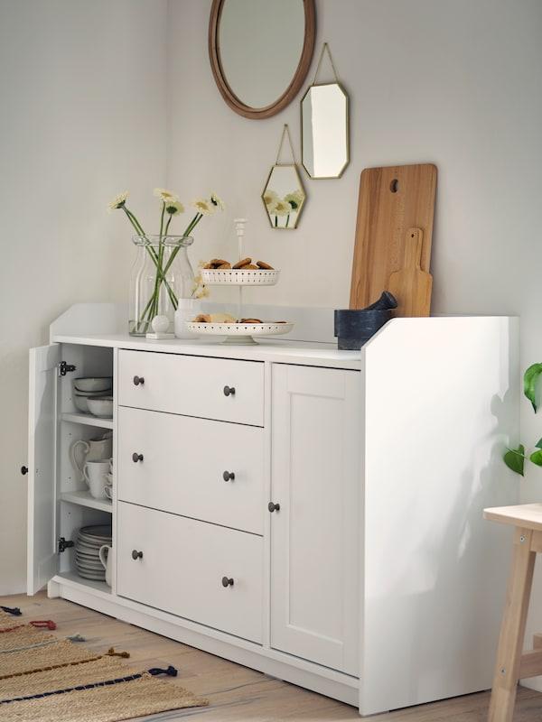 Rože v vazi, servirni pladenj s piškoti in deske za rezanje na beli kredenci. Nad kredenco so na steno pritrjena ogledala.