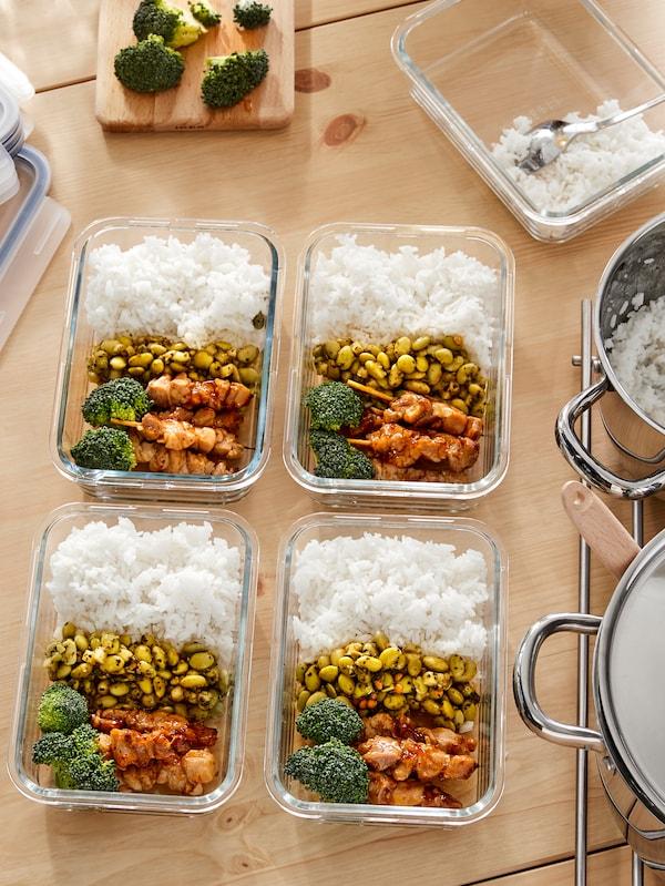 Unos recipientes de alimentos IKEA 365+ sobre una encimera con arroz, alubias, brócoli y brochetas de pollo.