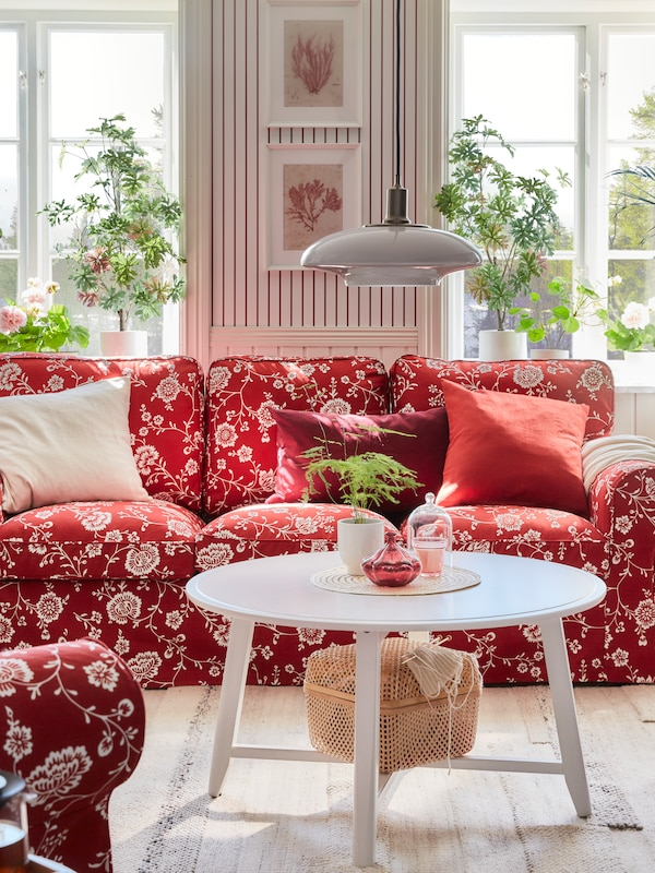 A red sofa with a white floral design in front of a window, with a pendant lamp above a round white table, and plants in the background.
