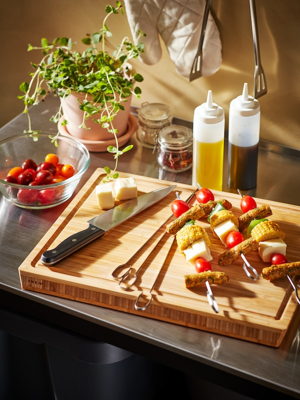 Prepped GRILLTIDER skewers on an APTITLIG butcher's block, surrounded by barbeque accessories on an outdoor-kitchen worktop.