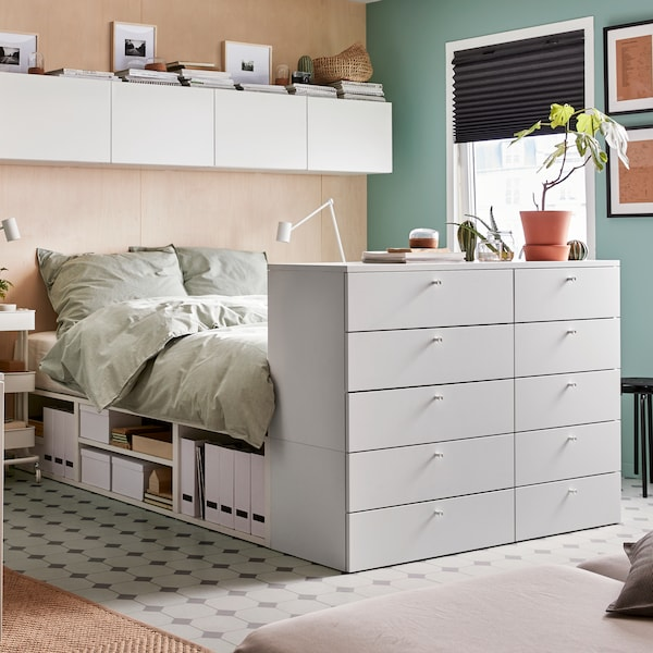 A bedroom with a white bed with built-in storage underneath and ten drawers at the end, and four white wall cabinets above.