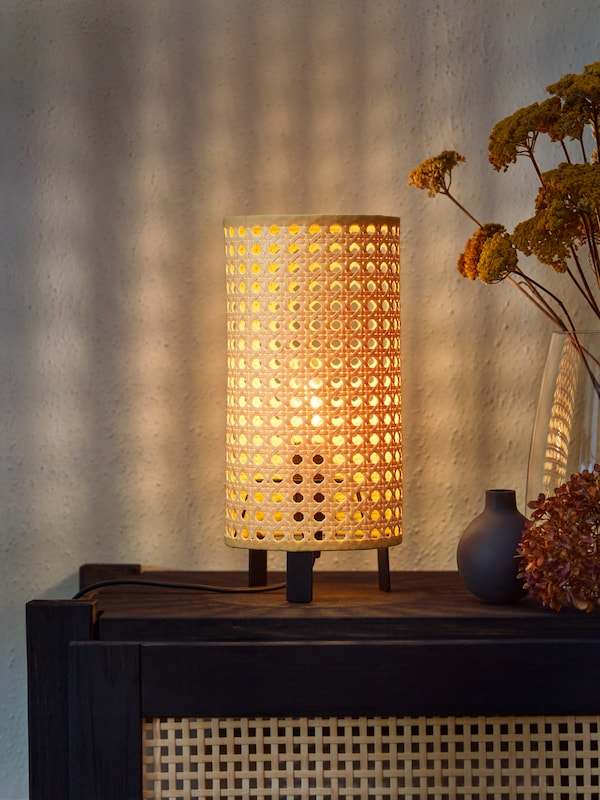 A beige and black SAXHYTTAN table lamp on top of a cabinet with doors casts patterned light on a wall and brightens a room.