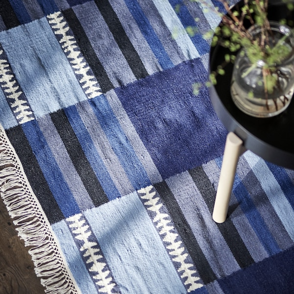 A rug in various shades of blue, black, grey and white, with a coffee table holding a few plant cuttings in a glass jar.