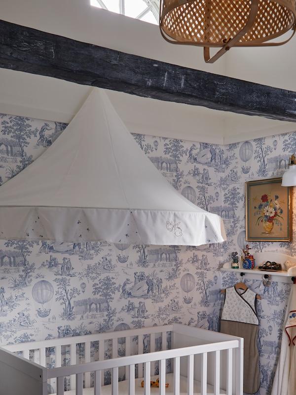 Børneværelse med en hvid sengehimmel over en hvid tremmeseng, en loftlampe af bambus og hvidt tapet med et blåt mønster.