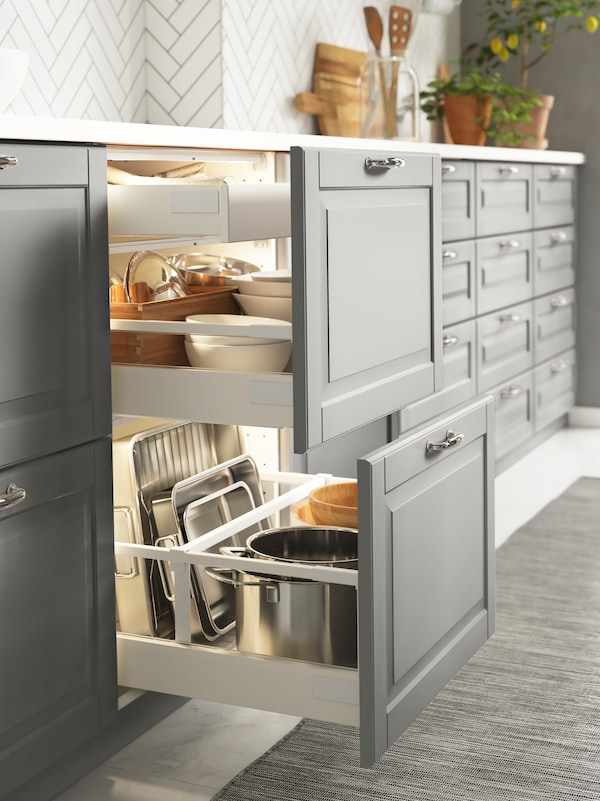 A grey BODBYN kitchen with two lower drawers pulled out to show kitchen accessories stored within.