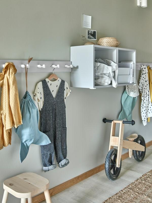 Des étagères EKET et des patères à crochets KUBBIS au mur sur lesquelles sont suspendus des vêtements d'enfants, avec un petit vélo et un tabouret en dessous.