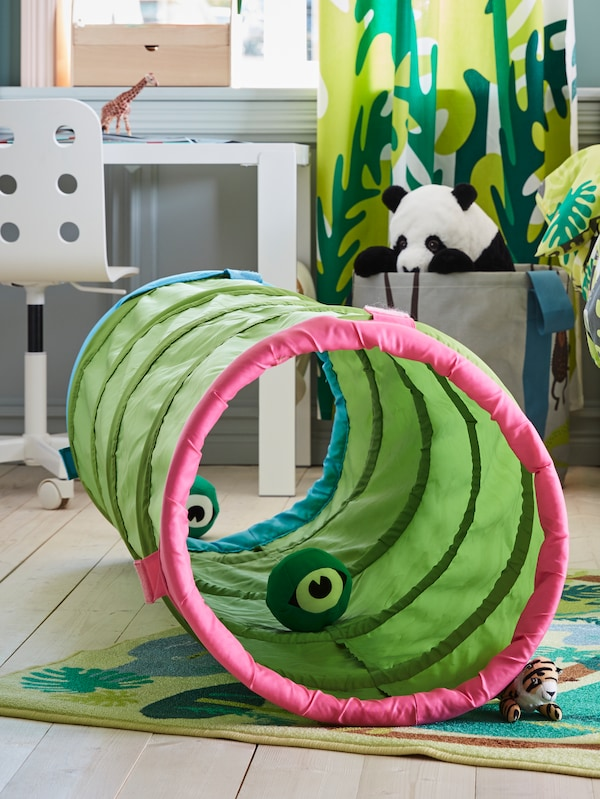 A green BUSA play tunnel with a pink border, inside a child's room.