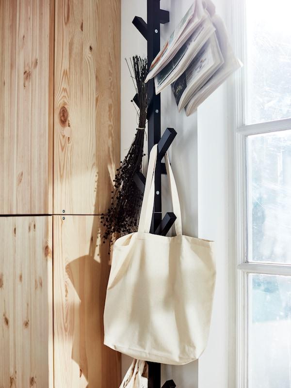 Stofftaschen Trockenblumen und gefaltete Zeitungen an einem TJUSIG Aufhänger.