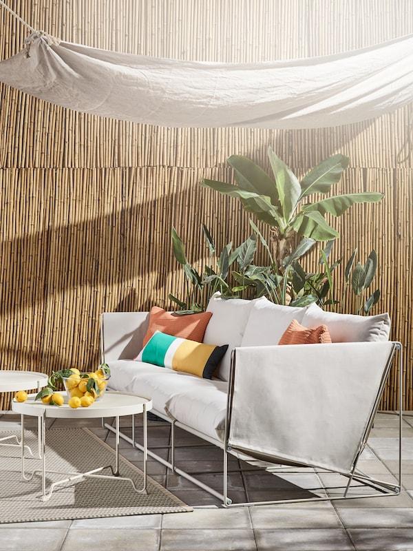 Una mesa de centro blanca sobre la que hay limones, un sofá con varios cojines y, tras él, un árbol.