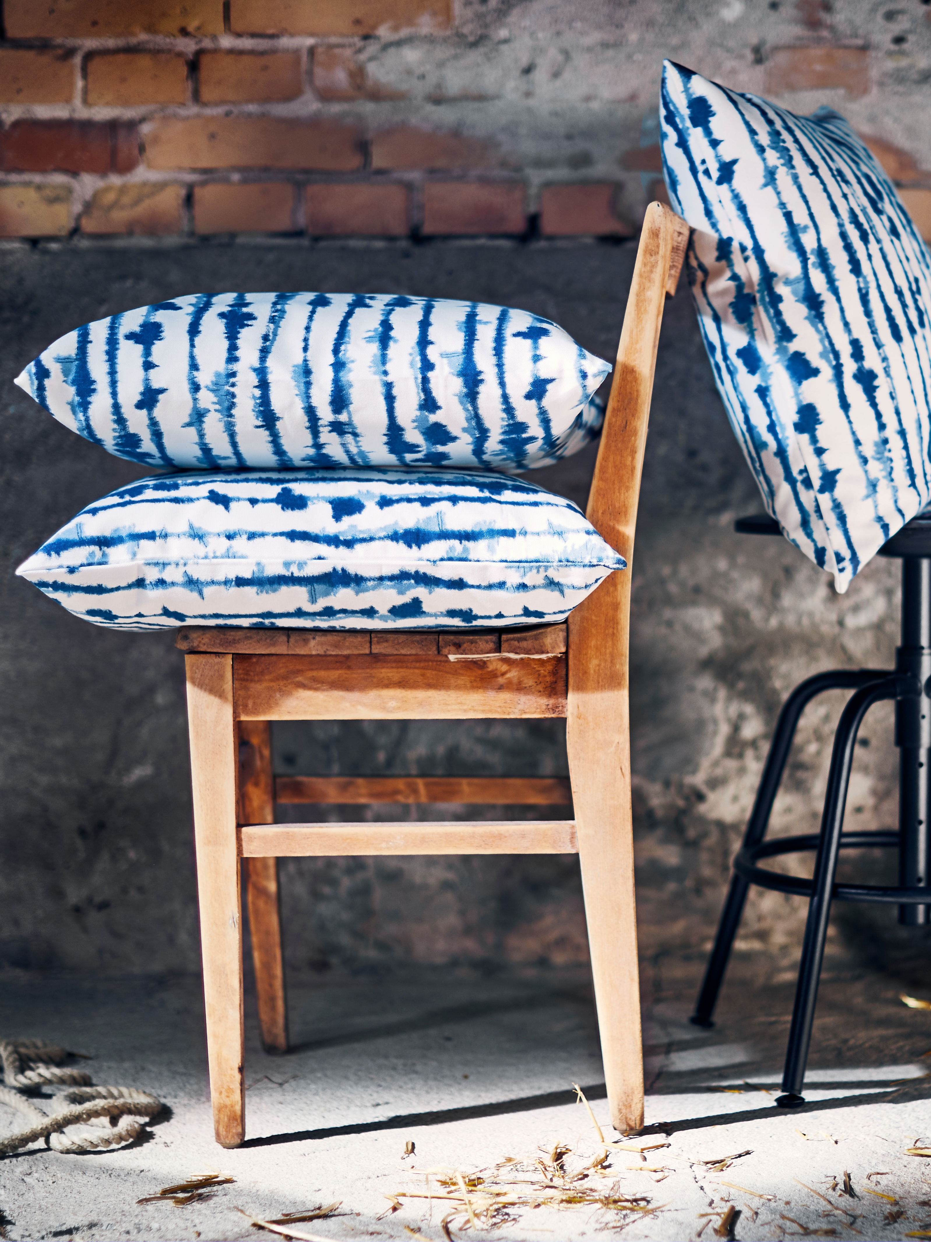 White/blue STRIMSPORRE cotton cushion covers on top of a vintage chair and a barstool.