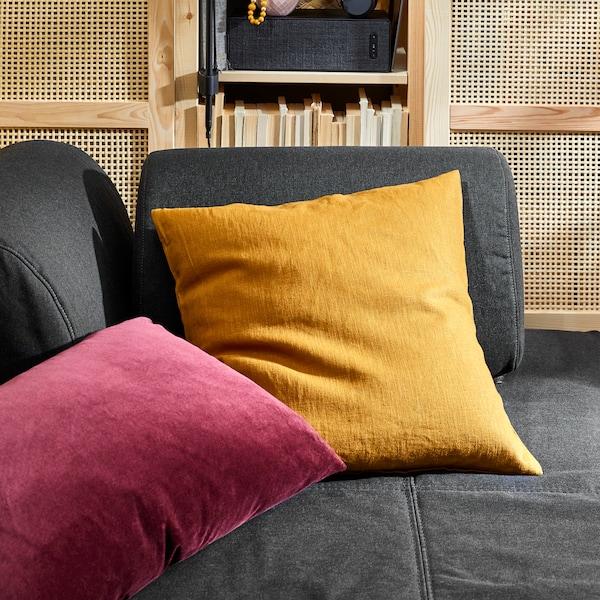 O pernă cu o față de pernă VIGDIS maro-auriu închis și o pernă roșie stau sunt așezate pe o canapea FLOTTEBO în fața unui corp IVAR.