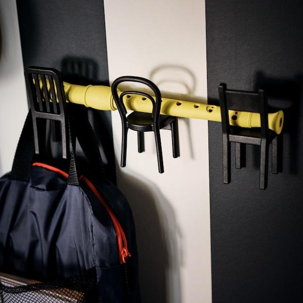 Ein breit in Schwarz und Weiß gehaltener Wandbereich mit einer Blockflöte, die über drei Miniaturstühle an schwarzen FJANTIG Haken liegt.
