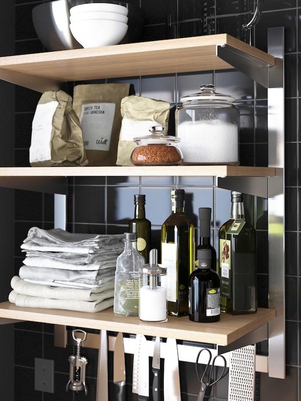 Trois tablettes ouvertes en bois servant à ranger des condiments, de la vaisselle et des serviettes de cuisine.