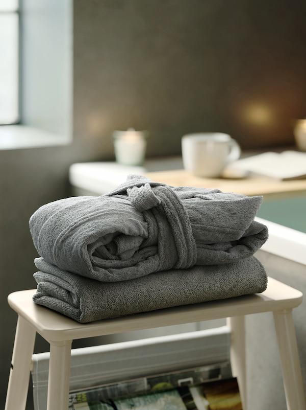 En stabel med en ROCKÅN badekåbe, der er lagt sammen, og et gråt håndklæde på en taburet af træ med opbevaring med magasiner.