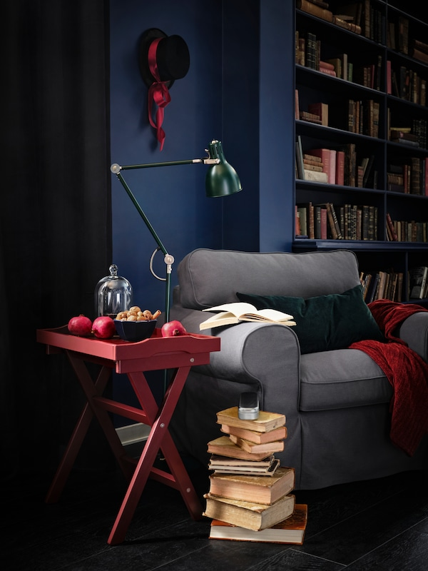 Books are piled up next to a cozy-looking EKTORP armchair with a red table and green lamp stood next to it.