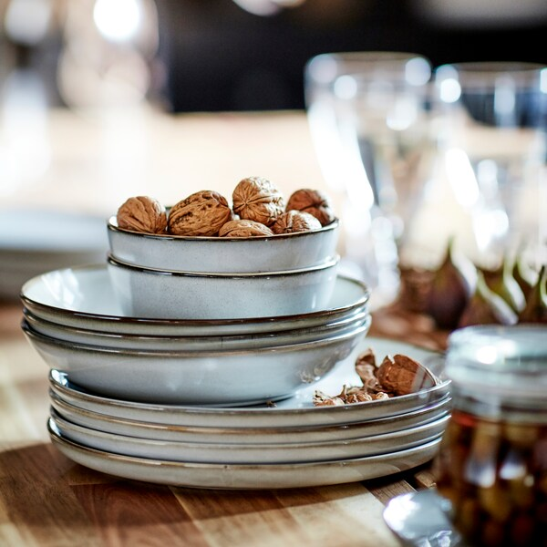 GLADELIG deep plates, bowls and plates in grey with a sandy glaze are stacked together. The top bowl contains walnuts.
