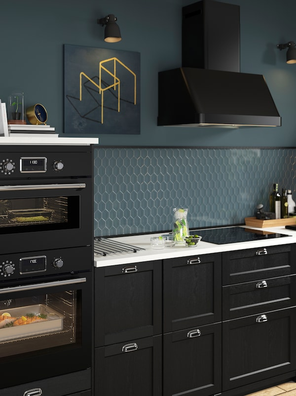 A black kitchen with blue walls, a black extractor hood, a white worktop, and a built-in microwave and oven.