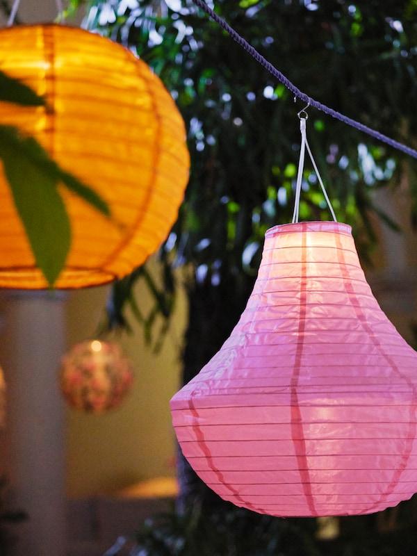 Due lampade a sospensione SOLVINDEN a energia solare in rosa e arancione appese a una corda in esterno, di sera.