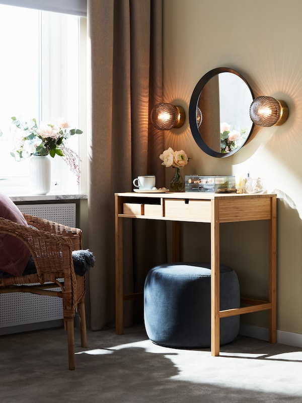 An armchair and a bamboo NORDKISA dressing table with a dark grey LANGESUND mirror mounted above it.
