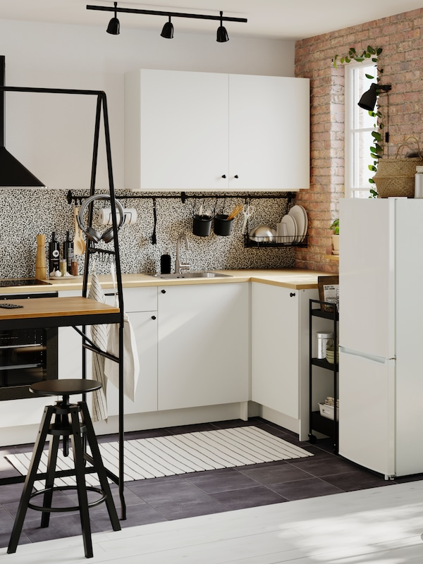 A small open-plan kitchen fitted with modules from the KNOXHULT series. A HÅVERUD table with storage ladder is on one side.