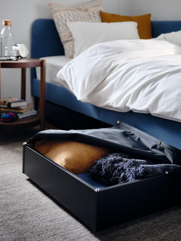 Sort sengeskuffe med en pude og et sengetæppe ved siden af et polstret sengestel med en hjørnegavl.