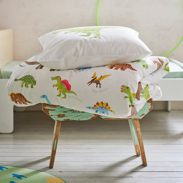 A stool with a folded duvet and pillow with JÄTTELIK quilt cover with a white base and a colourful dinosaur pattern.