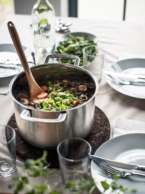 Kattilallinen vihanneksia pannnunalusen päällä ruokapöydällä.