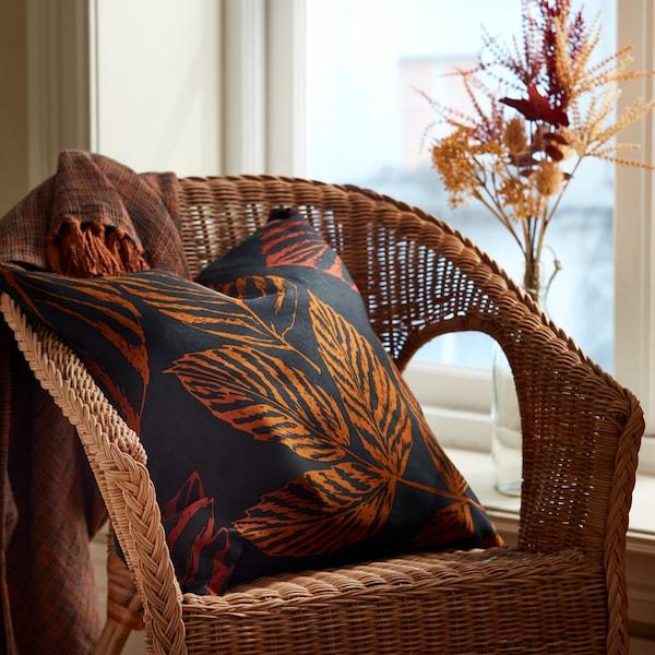 Une chaise en osier est placée contre une fenêtre. Un oreiller HÖSTKVÄLL à motifs de feuilles est posé sur la chaise. Une couverture HÖSTKVÄLL brune est étendue sur le dossier de la chaise.